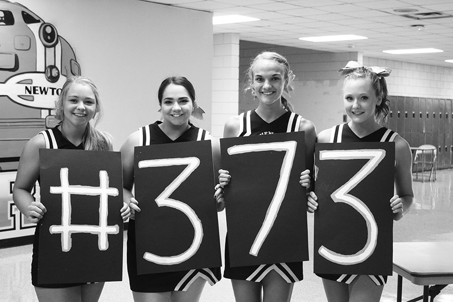 Cheerleaders show their support with #373 signs.