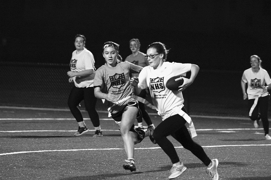 Sophomore Rebekah Nelson carries the ball as junior Mackenzie Parsons chases her flag during the first game on Friday Nov. 4. The sophomores beat the juniors in a close game to play the seniors in the championship game.