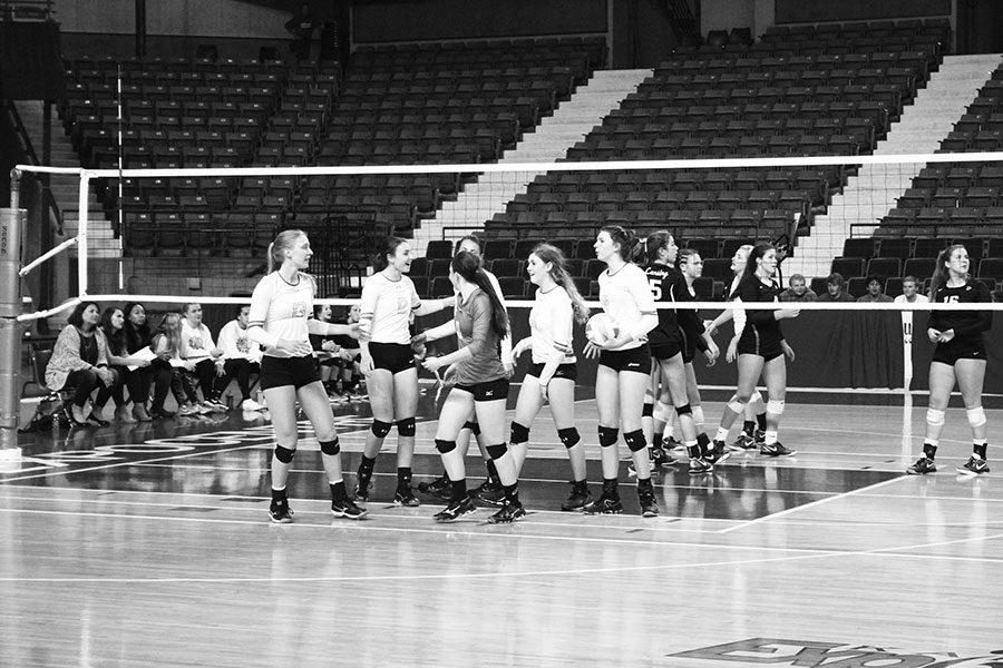 The volleyball team celebrates after they win a point at the state tournament in Topeka on Oct. 28. The team went 1-2 in pool play bringing the season to a halt.
