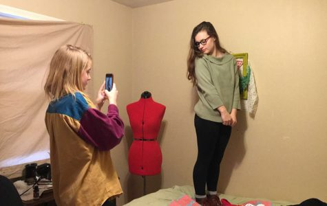 Quinn Rhodes takes a picture of Rebekah Nelson showing off a green sweater for their Twitter page.