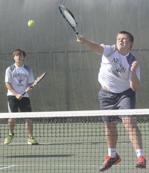 Then junior, Brandon Murrell, crushes a ball at the net while doubles partner, junior Cody Murrell, waits for the return at the Newton Invitational April 8th 2016.