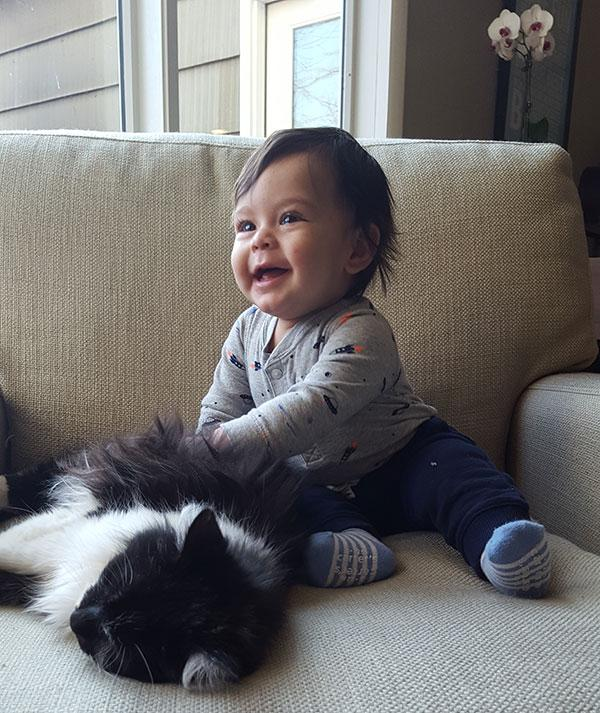Sophomore Kaete Schmidt's baby Theo Hernandez plays with the family cat. Hernandez is seven months old.