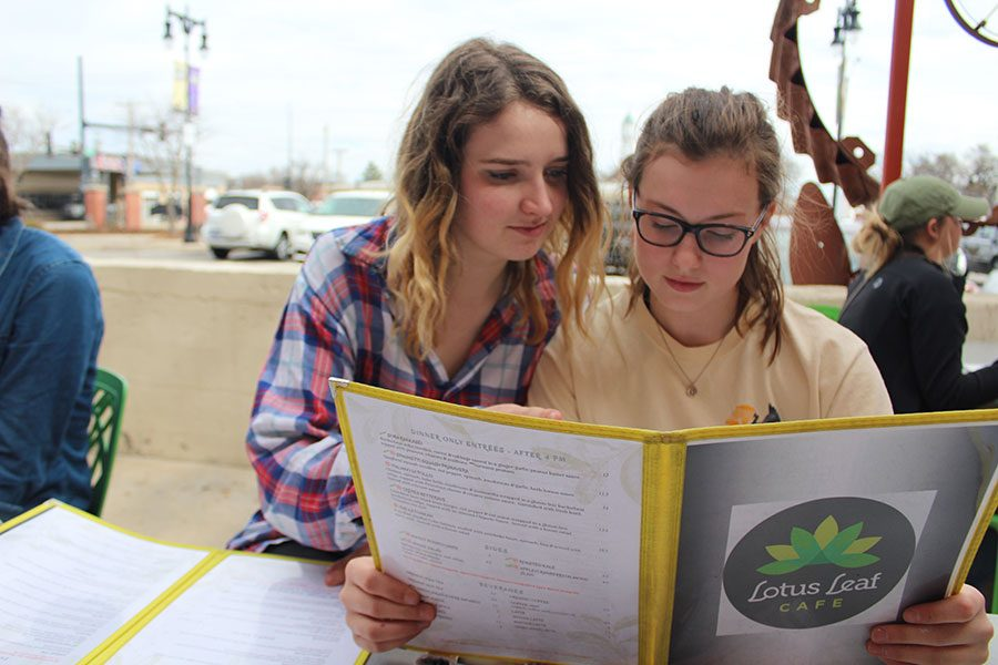 """Sophomore Rebekah Nelson and junior Zoe Siemens browse the menu before ordering their meals at the Lotus Leaf Cafe. The two had visited the cafe  before and were glad to return with the club. """"I tried the vegan burger. I always go for the veggie option but it's not very often that there's a vegan option and it was very nice."""" Nelson said."""