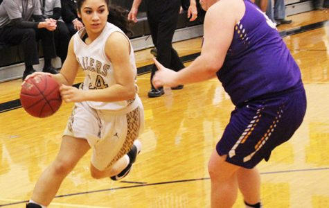 Trying to make a break to the basket, junior Taylor Brewer dribbles around a Valley Center defender. This was during the substate final on March 3.