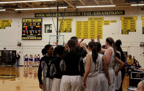 The girls basketball team huddles up during a timeout on Mar. 3. The girls won substate against Valley Center, continuing onto state.
