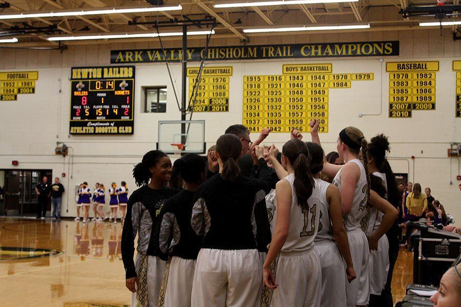 The+girls+basketball+team+huddles+up+during+a+timeout+on+Mar.+3.+The+girls+won+substate+against+Valley+Center%2C+continuing+onto+state.