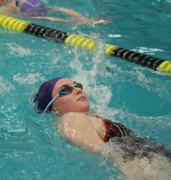 Junior Hannah Rogers moves smoothly through her lane, backstroking until the end of the pool. All of the swimmers were stretching and building up their muscles preparing for future swim meets.