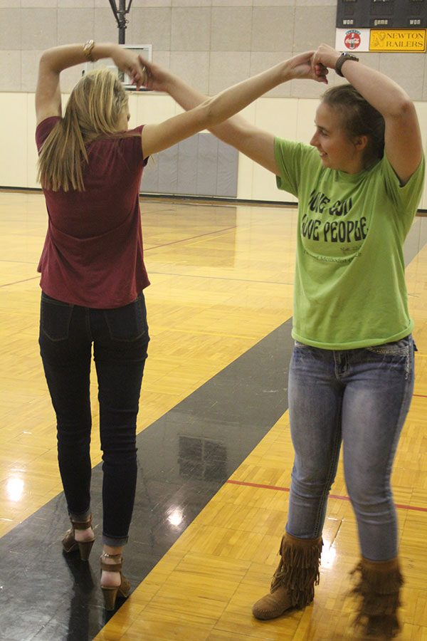 Sophmores Lauren Thompson and Taryn Wilson practice the pretzel during swing dance club on March 8.