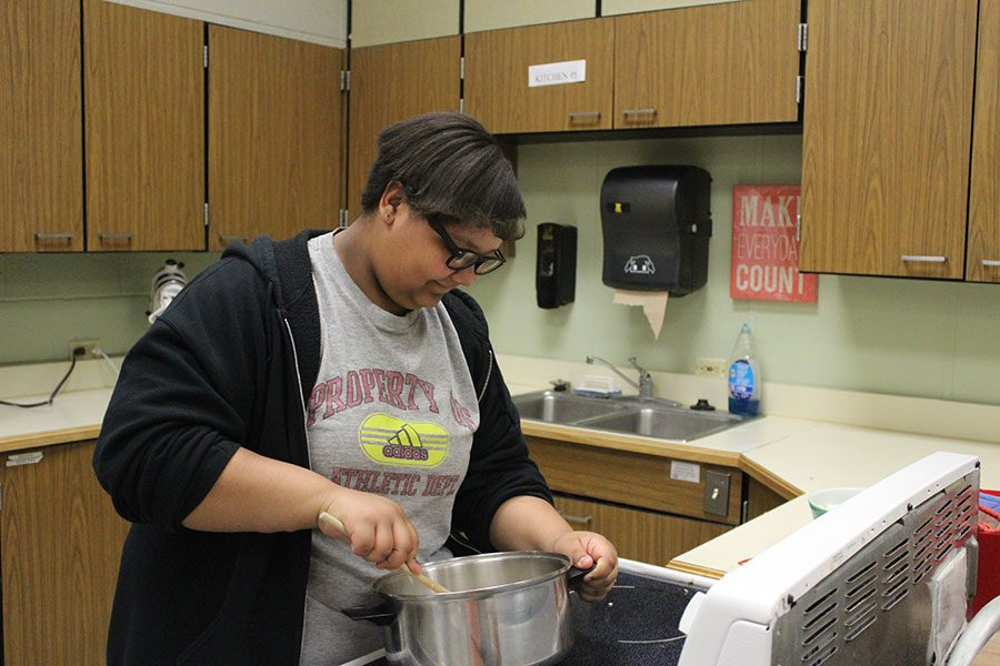 Focused on the mixture in the pot, sophomore Asia Hill stirs up the ingredients to make rice krispy treats. Hill joined the club later i the year.