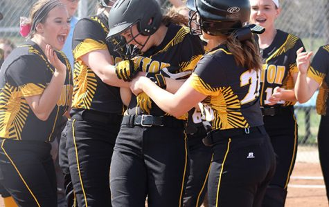 After hitting a homerun, the team celebrates and cheers on junior Kyndal Bacon as she runs into home.