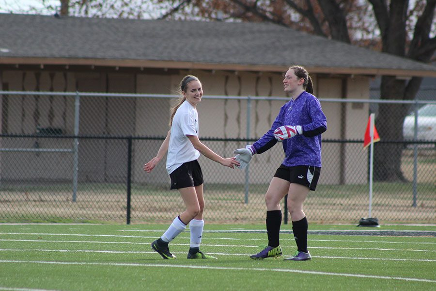 Filled with joy, Freshman Maddie Edson and Junior Megan Million high five after Edson scores the first goal of the game on a penalty kick.