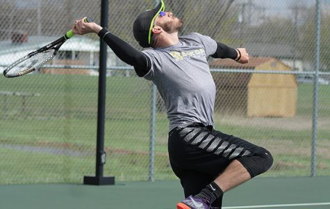 Senior Tyler Neufeld winds his arm back to return the ball to his opponent during a JV meet on April 5. Neufeld had been playing for the Hesston team due to a lack of Hesston players.
