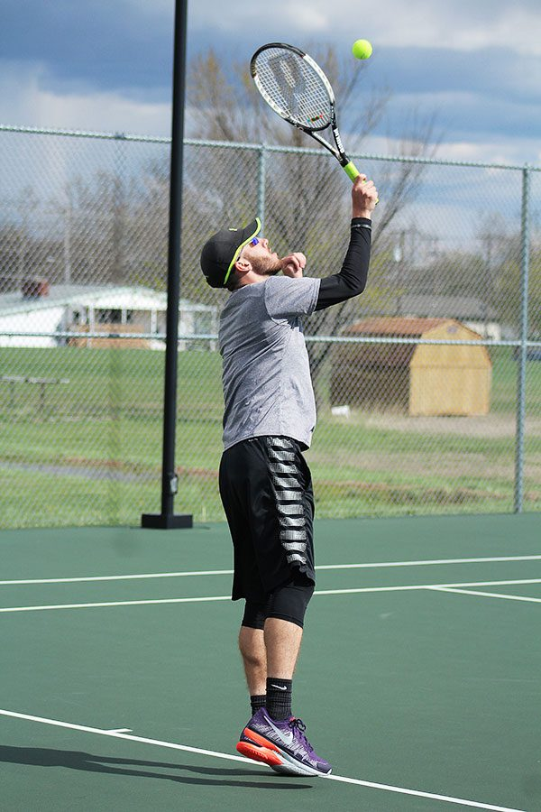 During a JV meet on April 5, senior Tyler Neufeld taps the ball with his racquet.