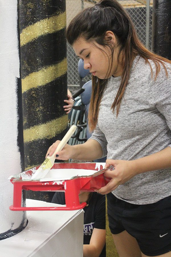 Focused hard, Gabriela Lara dips her paint brush in the white paint for the prom pillars this year. Lara was one of the very few students who made her own prom dress this year.