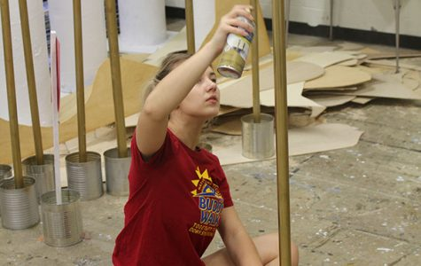 With prom in mind, junior Kaylee Anderson paints the poles to be used to rope off the walk way at Promenade. Anderson, along with junior Garrett Mick painted a total of 32 poles.