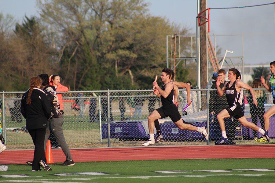 Running the second leg of the 4 x 100 meter relay, senior Kade Remsberg takes the lead at the Winfield Invitational.