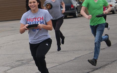 Seniors Dylan Shaw,  Riley Libel and junior Ivy Smith race to the finish line of their class's pancake race.