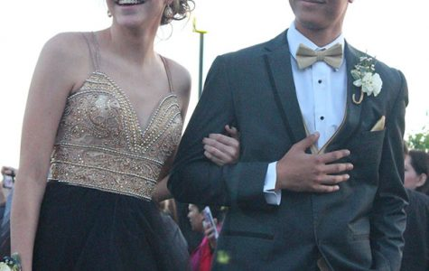 While the crowd watches, sophomore Kori Roberson and her date, senior Brandon Juarez-Autry walk down the path to prom.