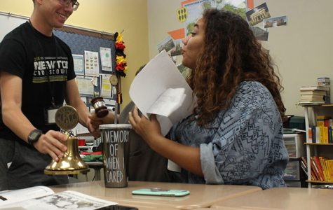 Seniors Erik Brown and Ellen Bradley joke around with the key club bell before the start of their very first meeting.