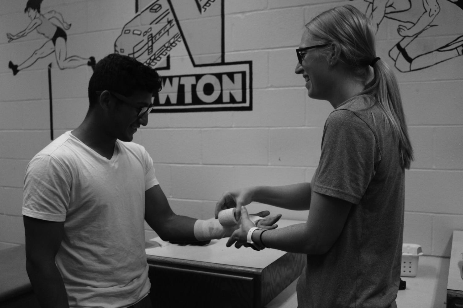 Senior Hervey Medina has his hand wrapped by the new athletic trainer, Elizabeth Brown. Medina injured his hand during a fall at soccer practice.