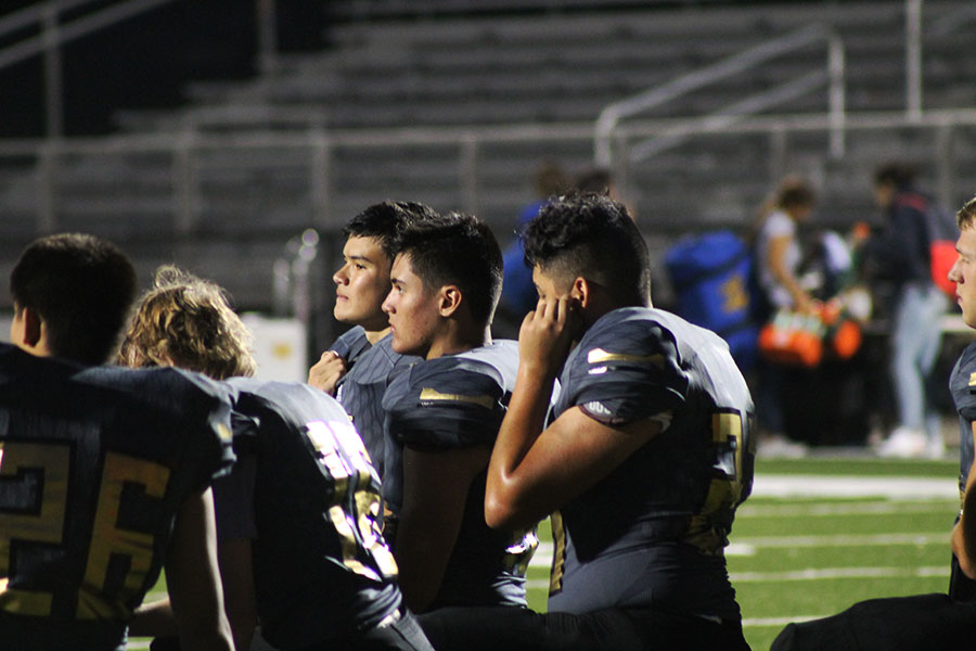 Sophomores Fletcher Hummingbird and Henry Claassen kneel and listen to the pep talk after the game. JV beat Hutchinson  36- 0 on Sept.11 at Fischer.