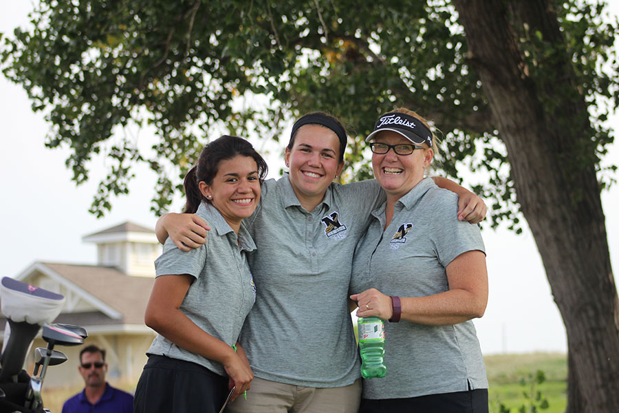 Juniors Ada Montano and Brynna Walton stand with coach Joanie Pauls and smile for a photo.