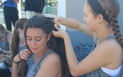 Prepping for the matches ahead seniors Kailei Sidebottom and Claudia Canete Molero sit down for a braiding session. That day Sidebottom played singles and Canete Molero played doubles with senior Valentina Samuelli.