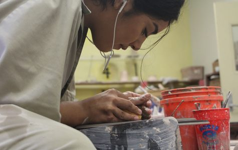 Maria Aboite leans in close to make sure she is centering her pot as well as possible.