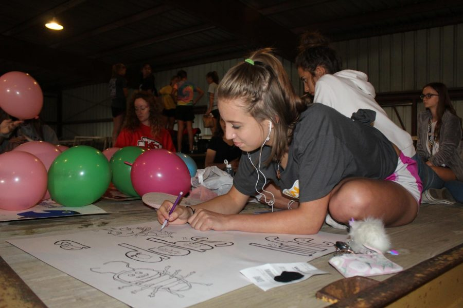 Sophomore+Natasha+Peterson+decorates+a+sign+for+the+cheerleaders+float.+