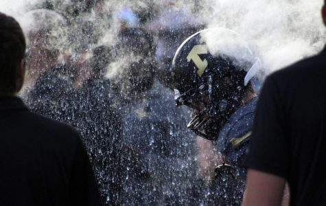 Through the fire and smoke, football player runs through foam cannon. Minutes later the homecoming game started.