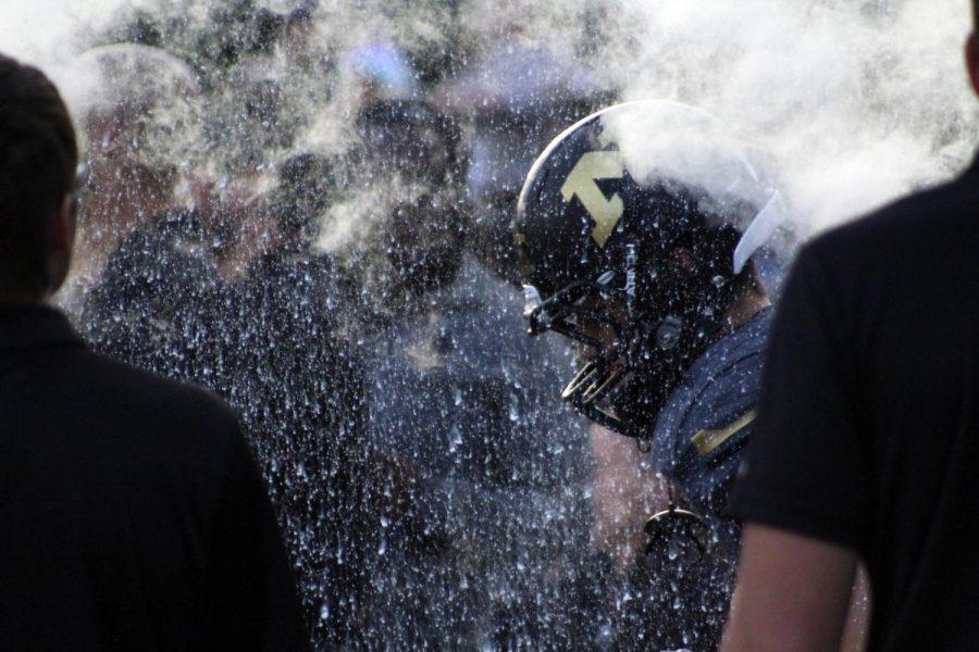 Through+the+fire+and+smoke%2C+football+player+runs+through+foam+cannon.+Minutes+later+the+homecoming+game+started.