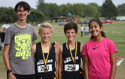 Junior Lylia Fernandez congratulates two of the Newton cross country participants. The two boys claimed the first two medals from the 7th grade boys race.