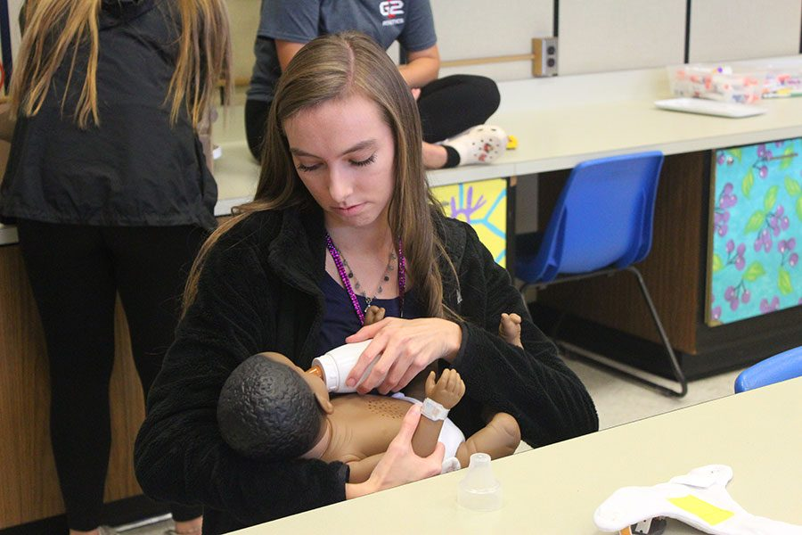 Students+in+family+studies+learn+how+to+care+for+a+child.+Junior+Kayte+Anderson+learned+how+to+properly+feed+a+baby.
