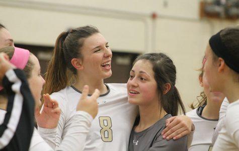 Marah Zenner and Caroline Barger smile after a sweep on senior night.