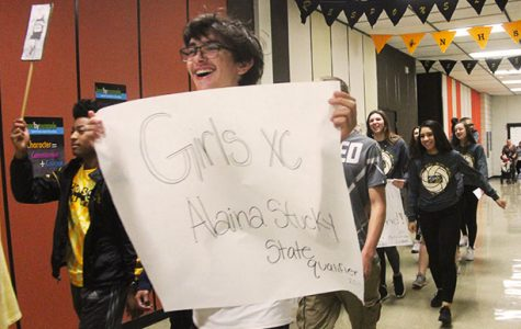 Sophomore Erik Jantz carries a poster supporting fellow team mate and state qualifier, Junior Alaina Stuckey