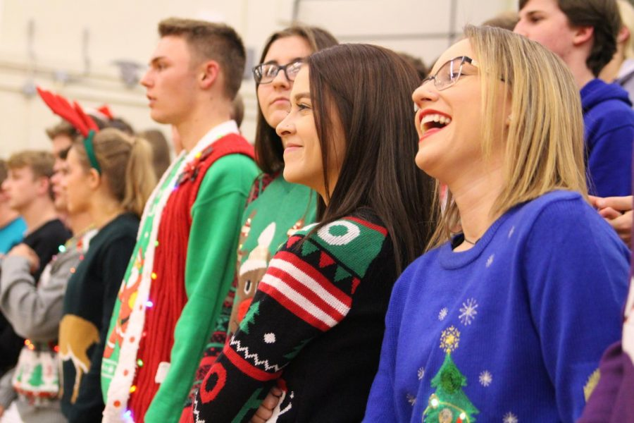 Seniors Mackenzie Parsons and Isabelle Saenz laugh in the student section at the home game against campus on Dec. 8. The theme for the night was Christmas.