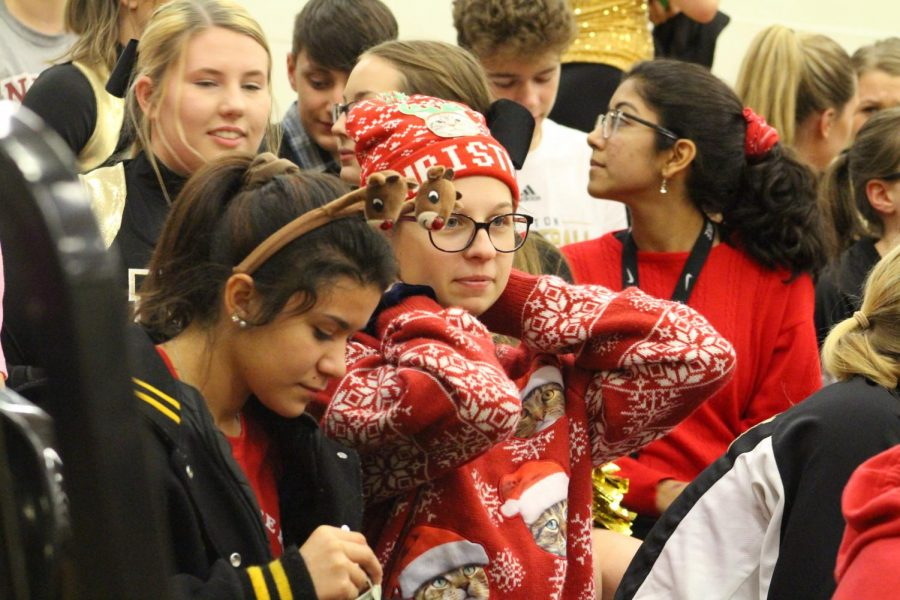 Tucked in the crowd of the student section juniors Ada Montano and Catie Arrowsmith watch the game. Students came decked in anything from festive sweaters, wearable lights and even bringing trees.