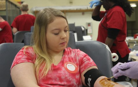 Watching with curiosity, senior Jasmine Powell gets her blood drawn during this years blood drive. This is Powell's third year participating, having done it since her sophomore year.