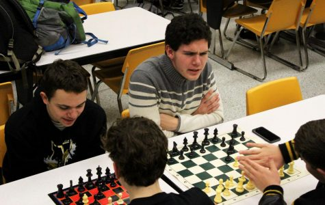 Arguing with his competitor sophomore Eli Blaufuss enjoys a game of chess next to sophomore Joshua Kennell who is playing his own game.