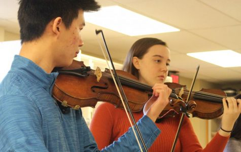 Seniors Jason Wong and Aubrie Nichols play the violin during a chamber orchestra performance at Chisolm Middle School. Wong led the others by playing the first few notes before every piece.