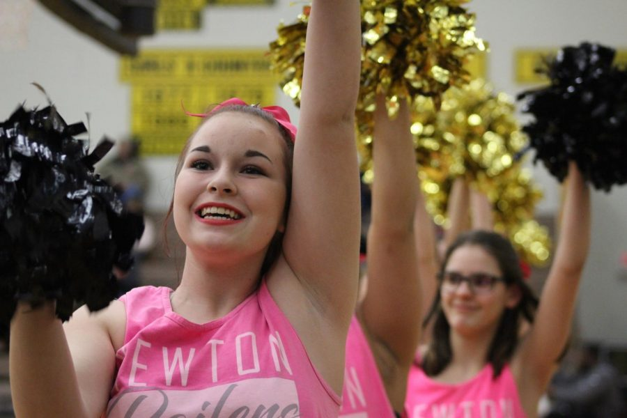 Dressed in all pink, junior Taleigha Funk cheers on the crowed at the start of the basketball game.