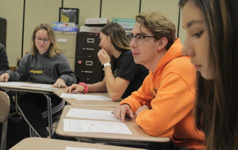 Senior Tanner DeGrado listens to his teacher Cathlina Bergman explain the  assignment in AP English on Feb. 23. The students were given old Valentine's Day candy while they worked.