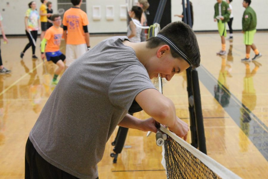 Freshman+Jonah+Schloneger+retrieves+his+birdie+after+it+got+caught+in+the+net+during+their+opponents+serve.+The+badminton+tournament+was+hosted+in+Ravenscroft+gym+starting+at+7+p.m.%0A%0A