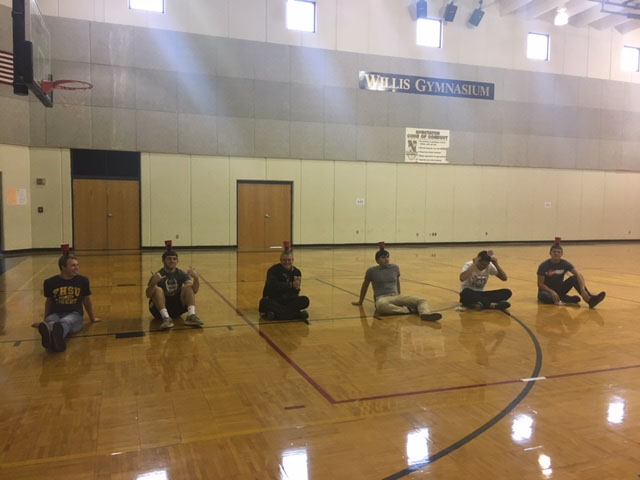 Seniors Gavin Powell, Ryan Watkins, junior Dante Harper, senior Richard Regier, juniors Zach Garcia and Jerik Ochoa sit on the floor in Willis Gym as they wait to begin the activity during a Railer Connections meeting.