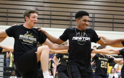 During their performance,  senior Christian Malcolm and Warren Dietz stand arm in arm, kicking out their legs with the rest of the dancers.