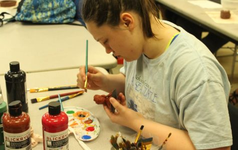 James concentrates as she tries to paint every detail on her clay figure. James chose Baby Groot as her piece.