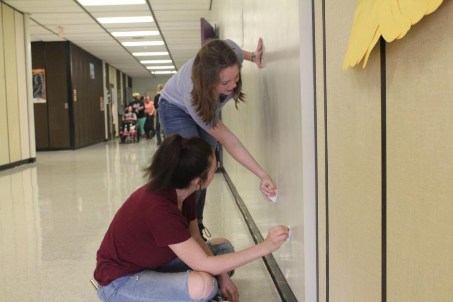 Sophomores Kaeden Thurber and Hailee Owens help their class clean the walls. They socialized and joked around while cleaning with their classmates.