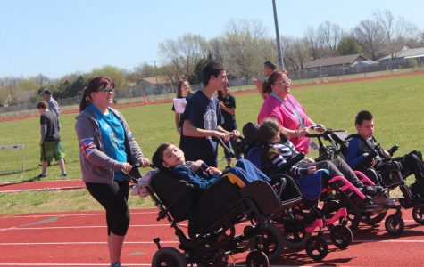 Students and teachers help each other down the track to finish out their event. Many parents and teachers came out to support the students in the track meet and ended the day with a cookout.
