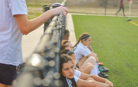 Players rest on the sidelines as the game continues. JV players watched the varsity game from the bleachers.