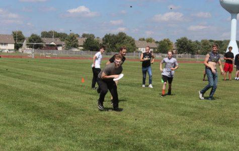 Junior Alex Ryan throws the frisbee to fellow student.